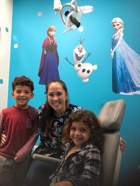 A hygienist with kids after their dental treatment at Oahu Pediatric Dentistry in Pearl City, HI