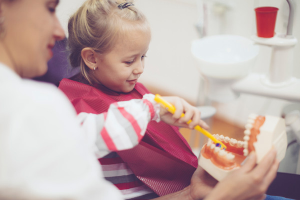 Young girl practicing brushing teeth with dentist watching