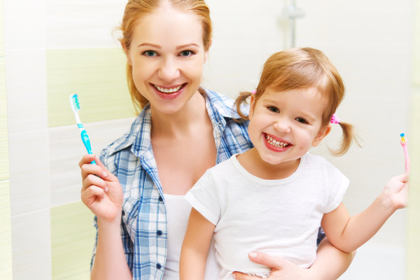 Mother and daughter smiling after brushing their teeth