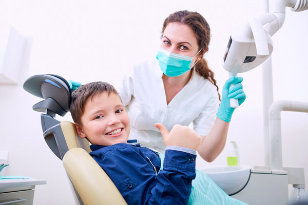 Child sitting in dental chair with doctor and giving a thumbs up