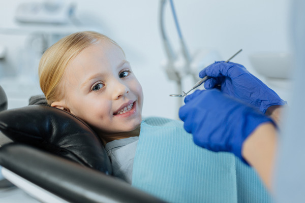 Blonde little girl smiling in dental chair