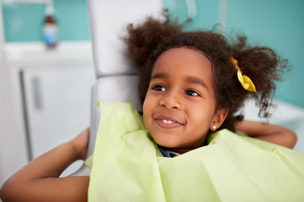 Adorable smiling girl in dental chair
